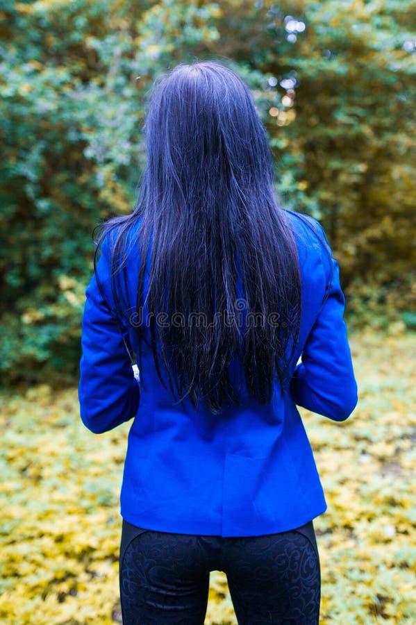 从后面的蓝色女孩 走在黑暗的森林后面视图的美女 蓝色长发后面视图 免版税库存照片