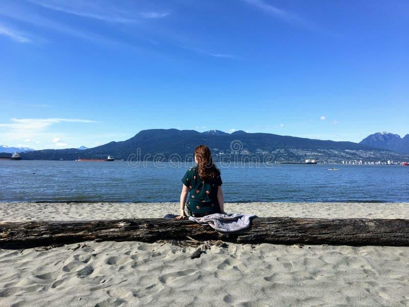 从后面观点的一美丽的年轻女人坐注册海滩在一美好的好日子,若有所思 库存照片
