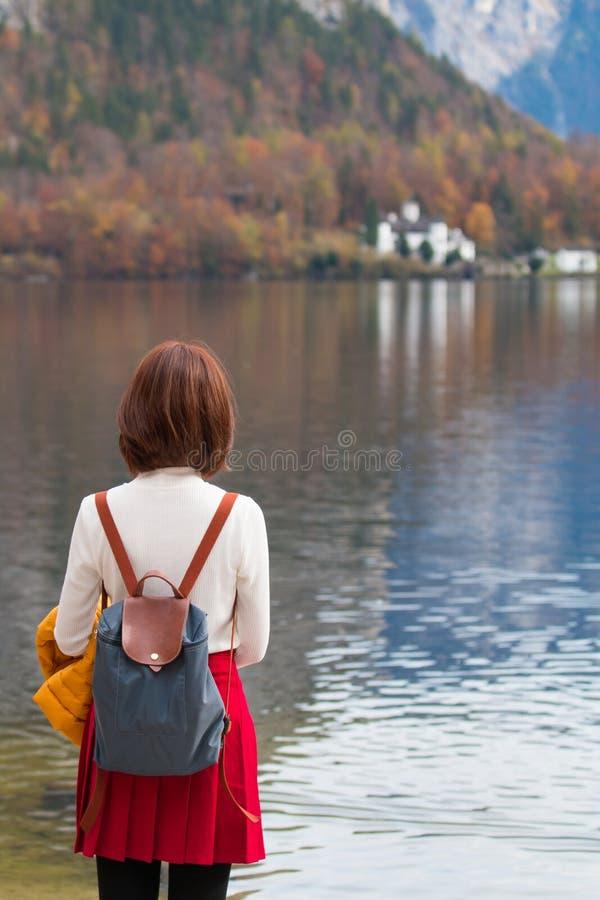 从后面身分的亚裔旅游旅行家女孩在Hallstatt湖奥地利在秋天;平安的自由放松概念 库存图片