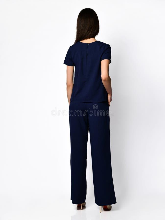 从后面 摆在有裤子时尚偶然夏天服装的新的深蓝女衬衫的年轻美女 库存图片