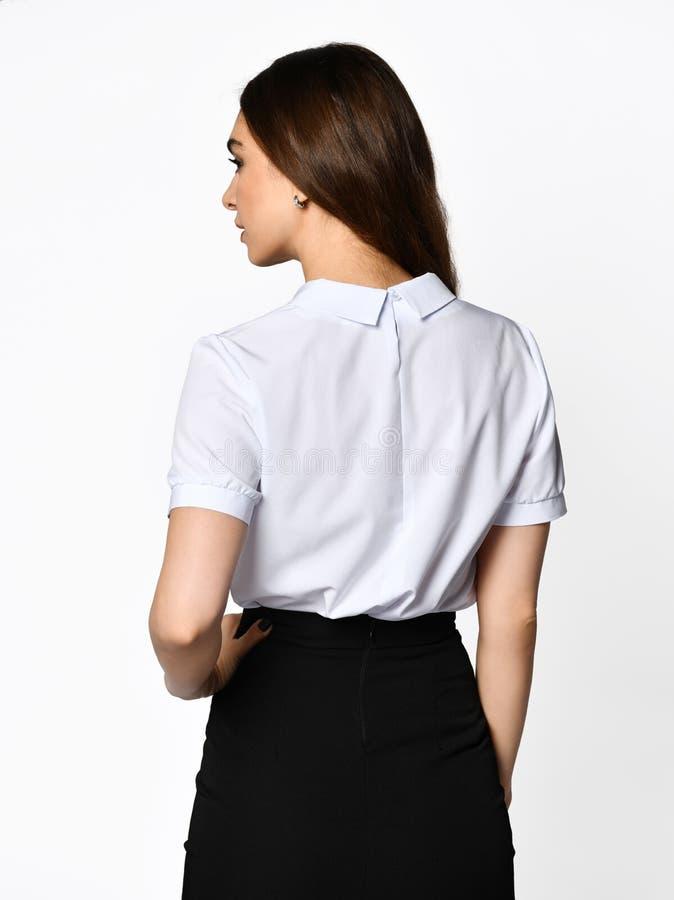 从后面 摆在轻黑暗的办公室衣服的年轻美女 轻的女衬衫和黑暗的铅笔裙子 库存图片
