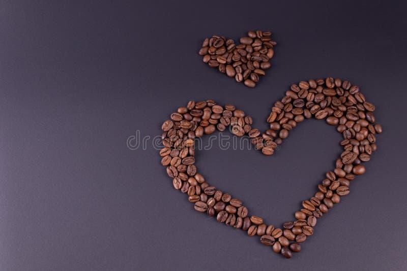 从咖啡排行的两心脏在背景右边的中心设置 免版税库存图片