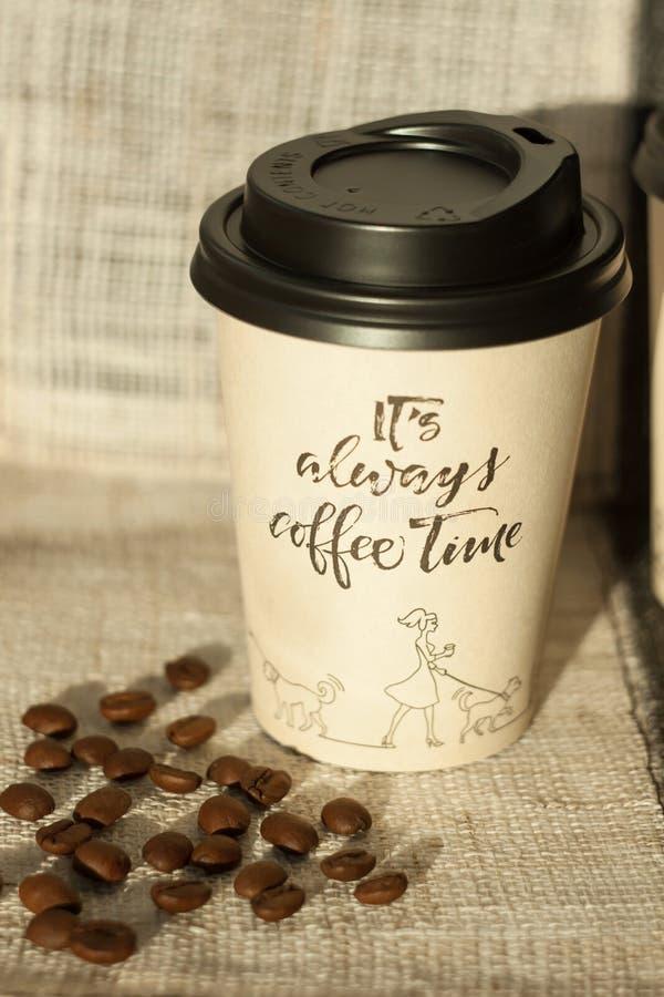 从咖啡馆的纸咖啡杯有在窗口附近的咖啡豆的 o 免版税库存照片