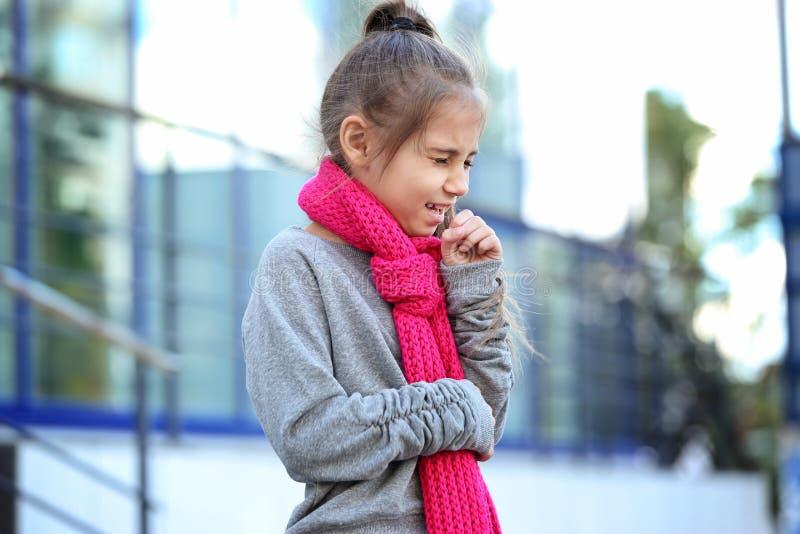 从咳嗽和寒冷的女孩痛苦 库存图片