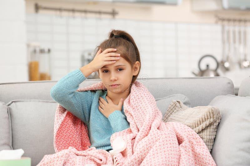 从咳嗽的女孩在沙发的痛苦和头疼 免版税库存图片