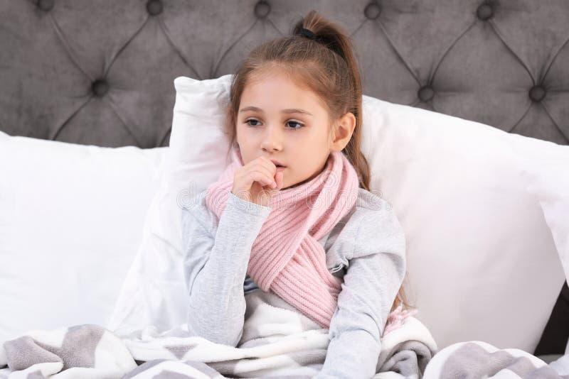 从咳嗽的女孩痛苦和寒冷在床上 免版税图库摄影