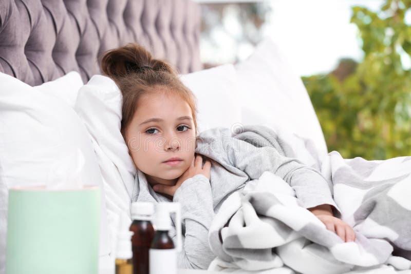 从咳嗽的女孩痛苦和寒冷在床上 图库摄影