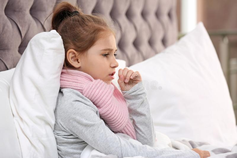 从咳嗽的女孩痛苦和寒冷在床上 库存照片