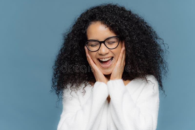 从喜悦的Overemotive女性接触面颊笑,保持眼睛闭上,不可能停止嘻嘻笑,安排蓬松卷发发型,穿戴在白色 免版税库存照片