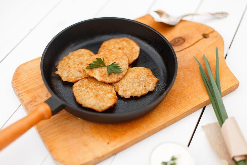 从土豆的薄煎饼在铸铁煎锅用葱 免版税图库摄影