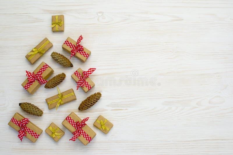 从圣诞树的构成由杉木锥体、金子和红色礼物制成在白色木背景 平的位置,顶视图 库存照片