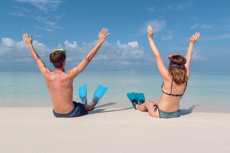 从在一个白色海滩供以座位的一年轻加上鸭脚板和面具的后面的图片在马尔代夫 透明的大海  免版税库存照片