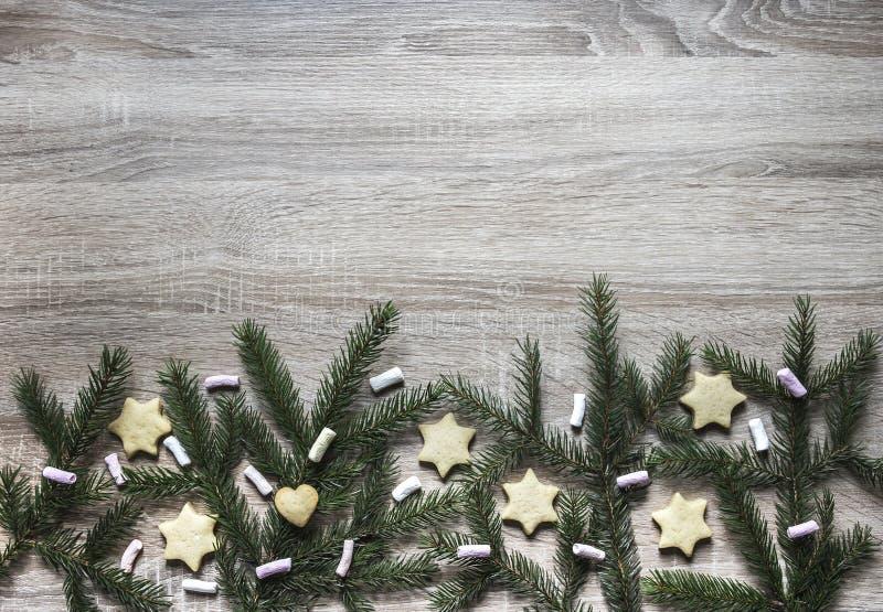 从在一张木桌上的底部是云杉的分支和蛋白软糖、姜饼干以星号的形式和心脏 图库摄影