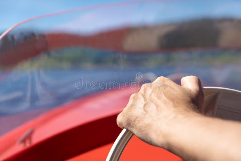从在汽艇,蓝色湖backgr的轮子的一只手关闭  图库摄影