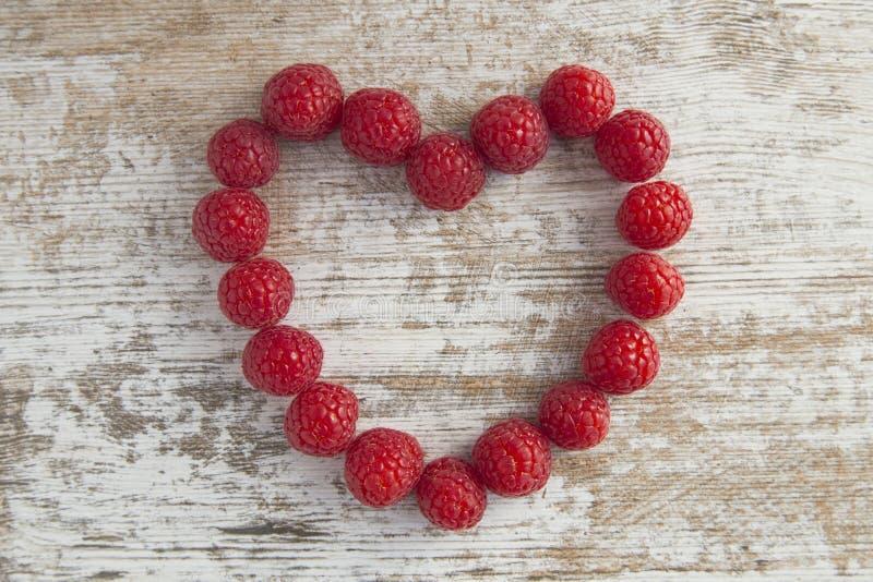 从在白色木背景的莓做的心脏 库存照片