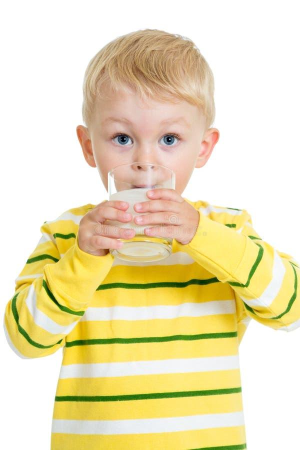 从在白色隔绝的玻璃的儿童男孩饮用的乳制品 库存图片