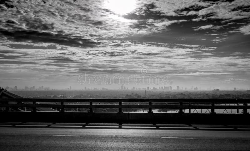 从城市桥梁的黑白被定调子的看法在河和天空和白色云彩附近的 哀伤,绝望和死亡背景 免版税库存图片