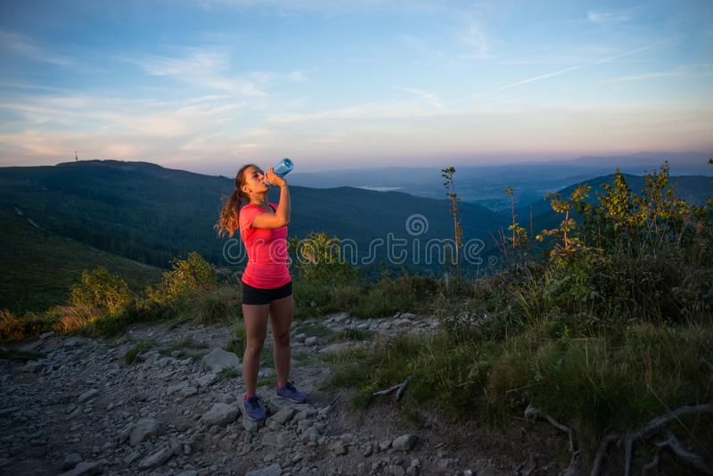 从塑料瓶的妇女足迹赛跑者饮用水 库存照片