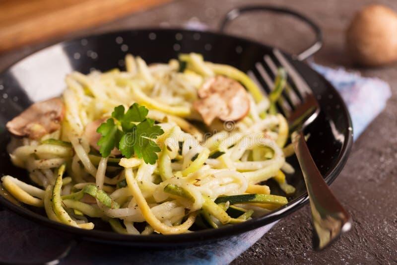 从夏南瓜和蘑菇酱油准备的平底锅意粉在木桌上 库存照片