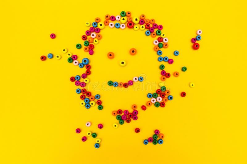 从多彩多姿的圆的玩具的微笑的小的人面带笑容在黄色背景 库存图片