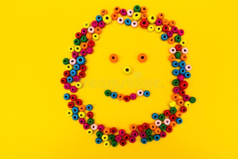 从多彩多姿的圆的玩具的微笑的面带笑容在黄色背景 免版税库存照片