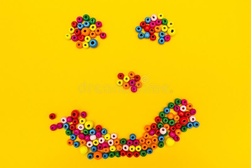 从多彩多姿的圆的玩具的面带笑容在黄色背景 库存图片