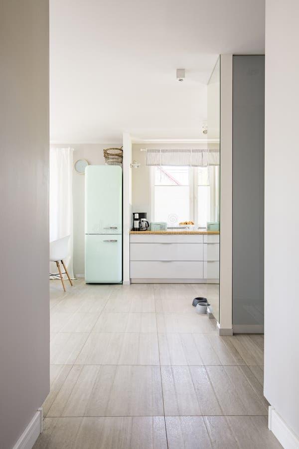 从大厅的看法与窗口a的明亮的宽敞厨房内部的 图库摄影