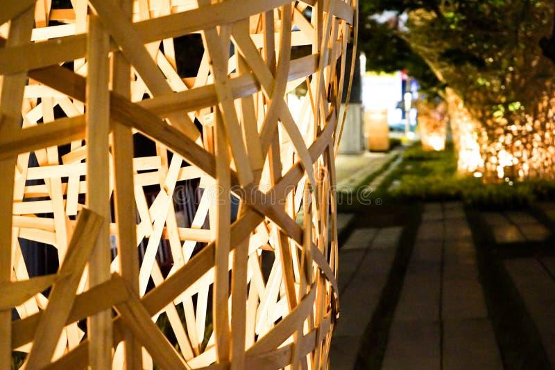 从大木棍子装饰的艺术在树附近同心协力与钨光的夜徘徊  图库摄影