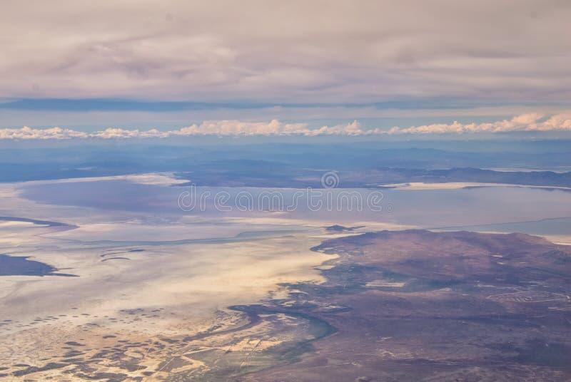 从大盐湖的飞机的鸟瞰图落矶山脉范围、清扫的cloudscape和风景的在白天在Spr 免版税库存照片