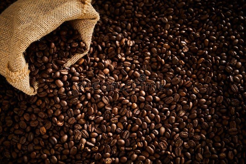从大袋溢出的黑暗的烤咖啡豆 图库摄影
