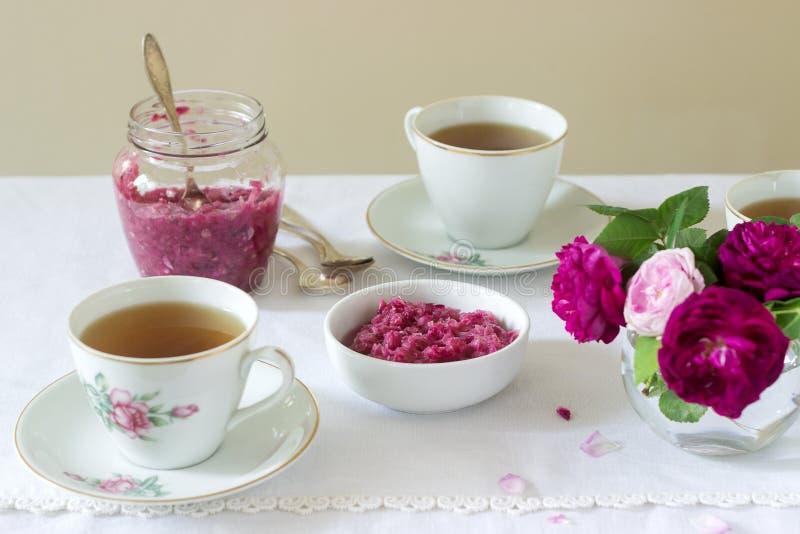 从大马士革的瓣的果酱上升了,一个杯子绿茶和一个花瓶在一张轻的桌上的玫瑰 土气样式 免版税库存图片