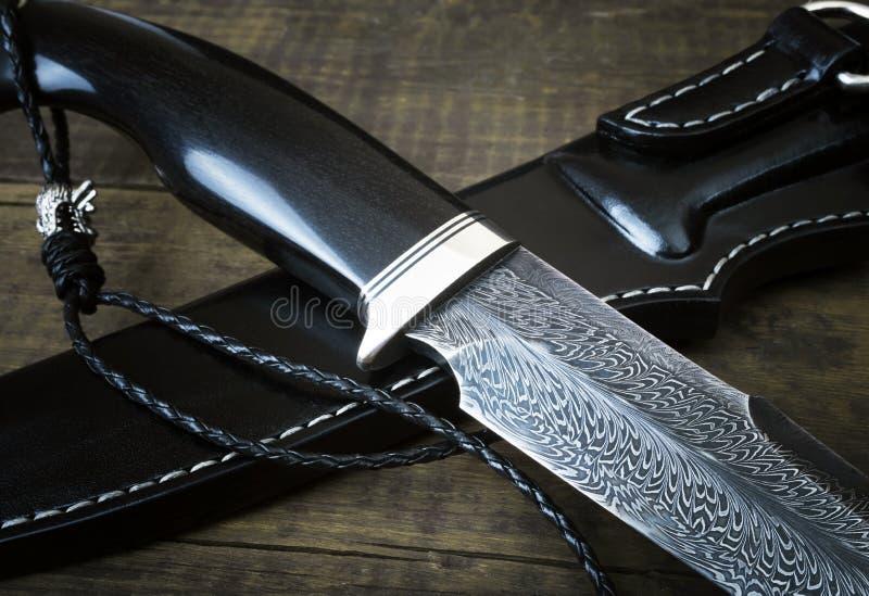 从大马士革马赛克的猎刀在木背景 手工制造皮革的鞘 库存图片