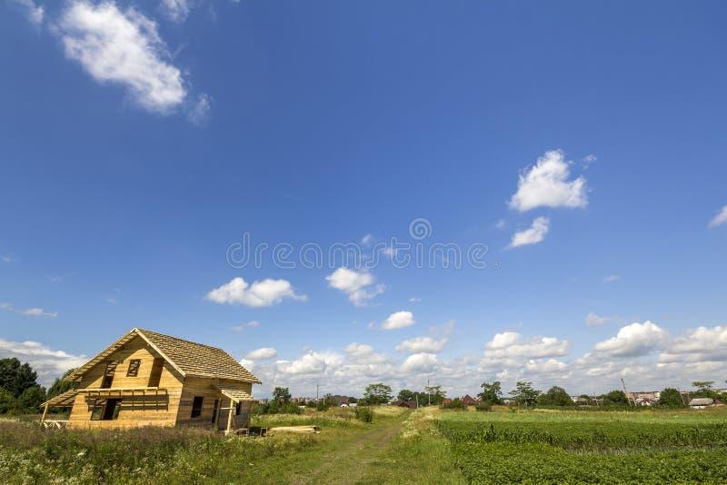 从天然材料的新的木生态不完成的村庄建设中在遥远的村庄和蓝色的绿色领域 免版税库存图片