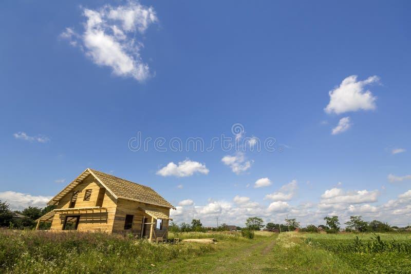 从天然材料的新的木生态不完成的村庄建设中在遥远的村庄和蓝色的绿色领域 图库摄影
