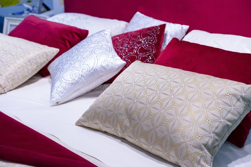 从天鹅绒和锦的装饰枕头在床上在卧室 库存图片