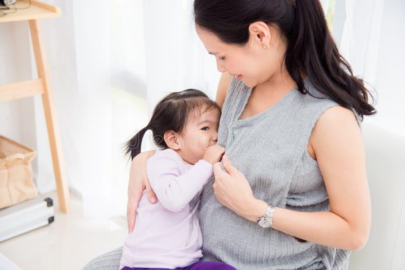 从她怀孕的母亲乳房的女孩饮用奶 库存照片