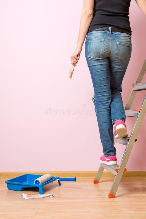 从妇女后面的照片有站立在活梯的刷子的 库存照片