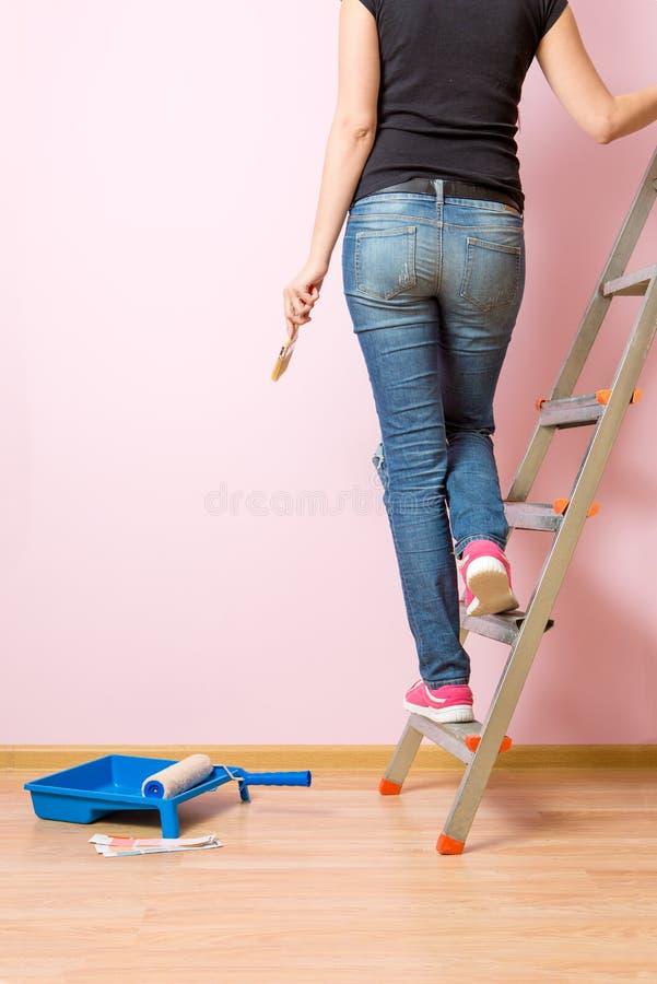 从妇女后面的照片有站立在活梯的刷子的 免版税图库摄影