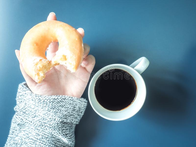 从妇女手的顶视图有布料举行的在whi的无奶咖啡 库存图片