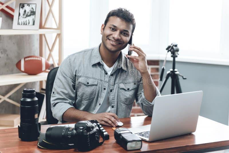 从家的印地安愉快的年轻人摄影师工作 库存照片