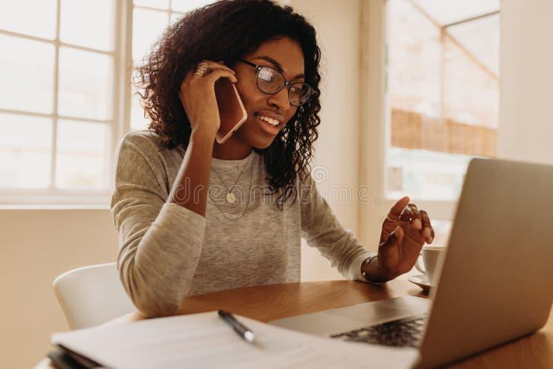 从家的妇女企业家处理的事务有手机的 库存图片