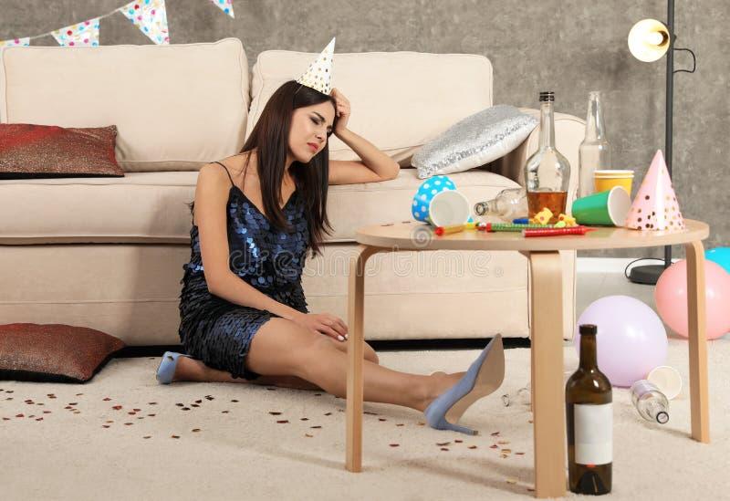 从宿酒的年轻女人痛苦在杂乱屋子里 库存图片