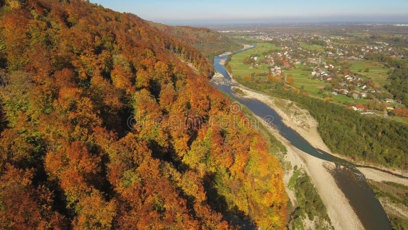 从寄生虫的空中,顶视图:飞行在与森林和河的山 免版税库存照片