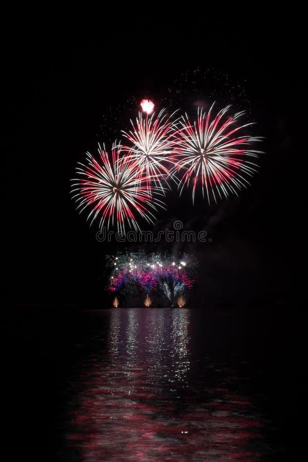 从富有的烟花的五颜六色的星在有湖反射的布尔诺的水坝 免版税库存图片