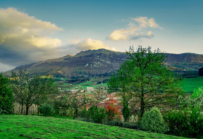 从小山上面的美丽的景色  谷的村庄 树在有天空蔚蓝和白色云彩的早期的春天 震动山的阳光 免版税图库摄影