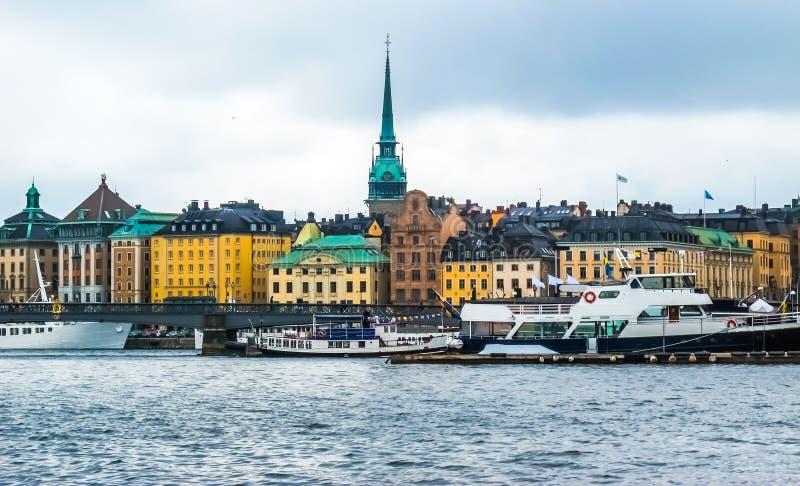 从小船的全景在江边房子在Gamla斯坦、游船和Skeppsholm桥梁有金黄冠的 斯德哥尔摩 库存图片