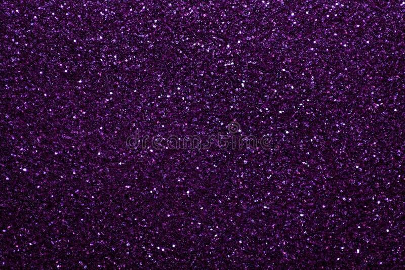 从小衣服饰物之小金属片的黑暗的紫色闪耀的背景,特写镜头 从纺织品的精采发光的背景 免版税库存照片