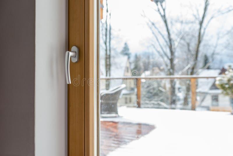 从屋子的看法通过与把柄的一个闭合的阳台窗口在与一把藤椅和楼梯栏杆的一个多雪的大阳台 免版税库存照片