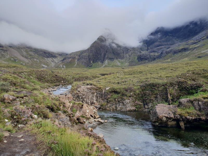 从山的河与暴风云 库存照片