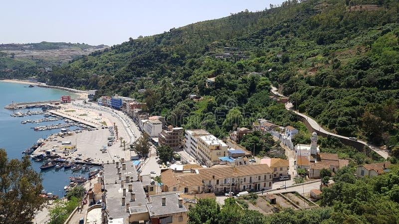 从山脉到渔船、小船港和蓝色地中海的全景 斯基克达 阿尔及利亚 2018年4月28日 库存图片